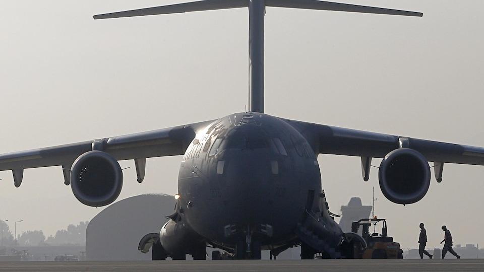 Deux militaires marchent vers un avion photographié de face.