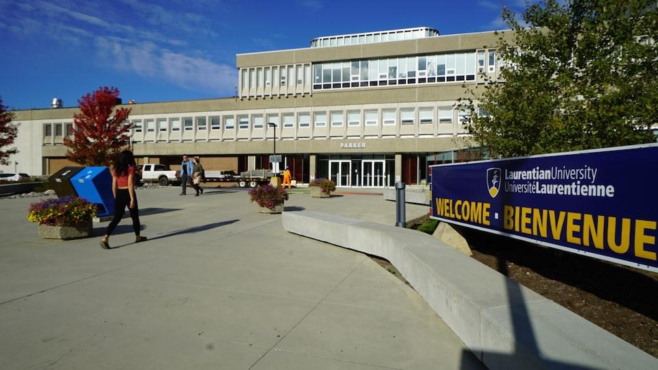 Des étudiants marchent vers l'entrée de l'édifice de l'université.