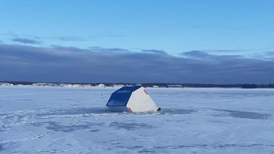 Une cabane d'éperlans flotte sur la glace.