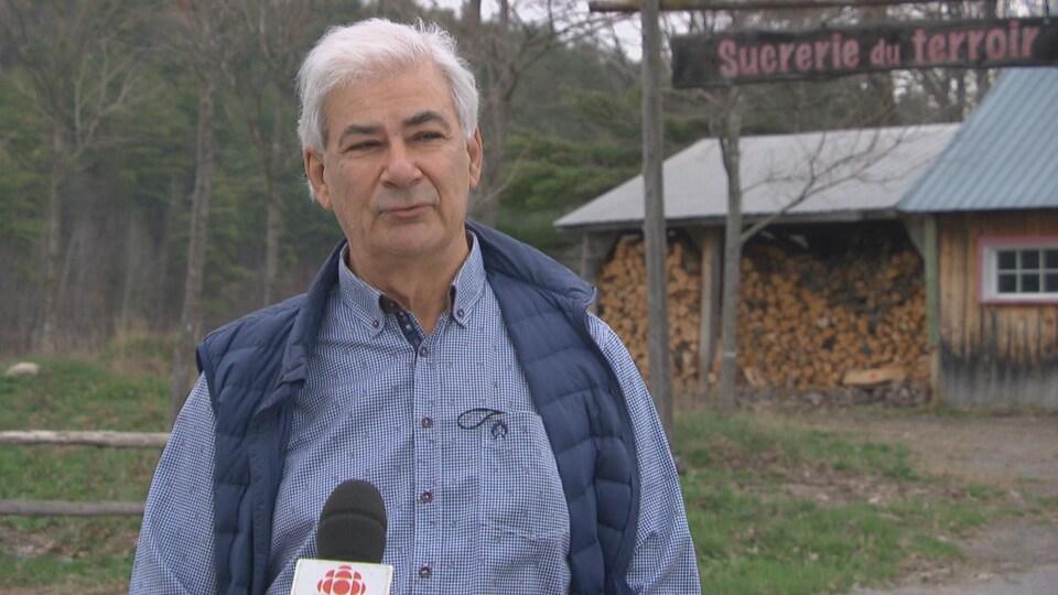 Un homme parle devant un micro, en entrevue avec ICI Ottawa-Gatineau.