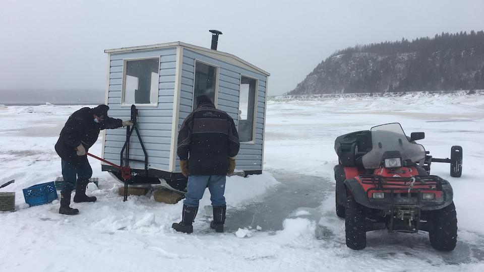 Des pêcheurs déplacent une cabane sur la glace.