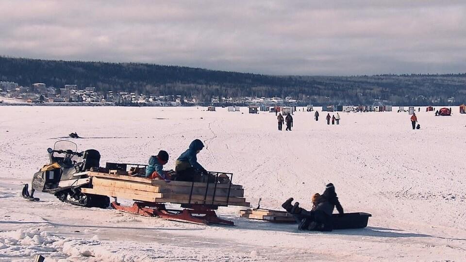 Une motoneige stationnée sur la glace avec une remorque contenant du bois pour bâtir une cabane de pêche.