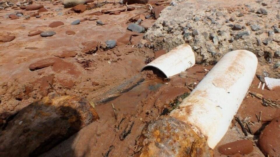 Deux tuyaux blancs émergent de la pierre sur la plage des Îles, et laissent entrevoir un câble enfoncé dans l'eau.