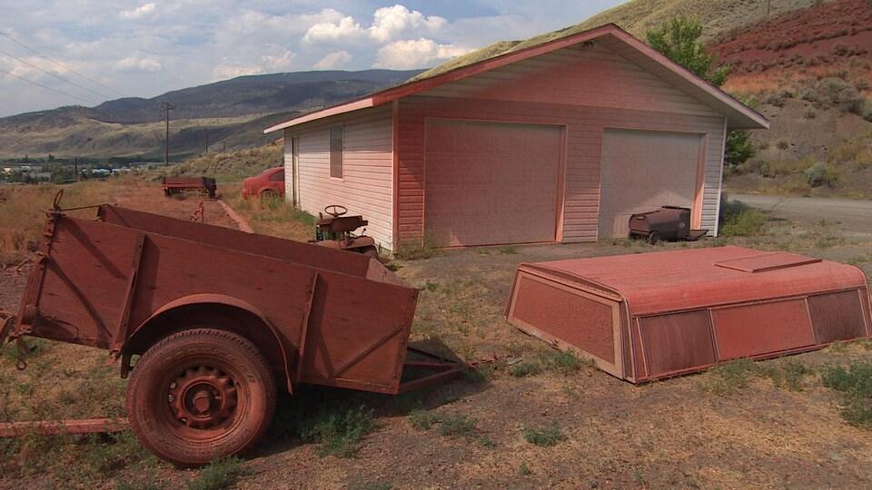Un garage, une remorque et une voiture recouverts d'une substance rouge.