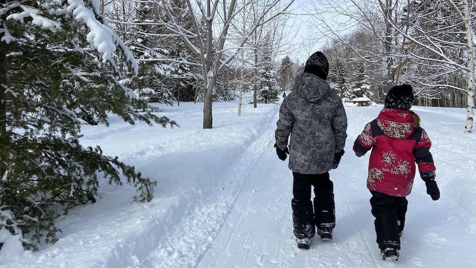 Deux enfants se promènent dans un sentier enneigé.