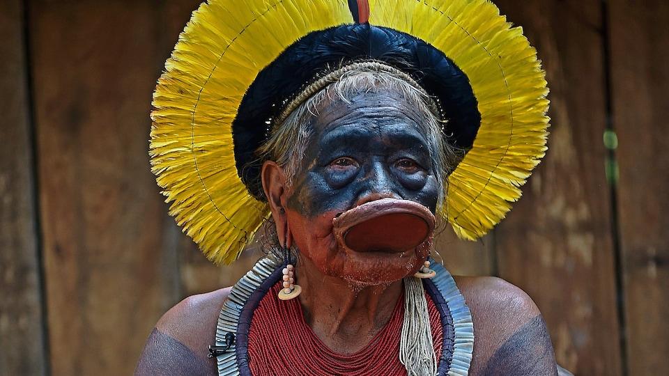 Le chef autochtone Raoni Metuktire est assis sur une chaise dans ses habits traditionnels.