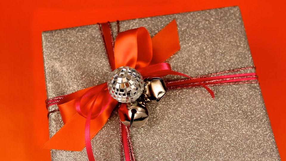 Photo d'un cadeau de Noël enveloppé de papier brun et entouré de ruban et d'une boucle rouges.