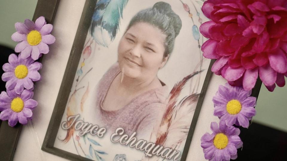 Une image de Joyce Echaquan dans un cadre avec des fleurs.