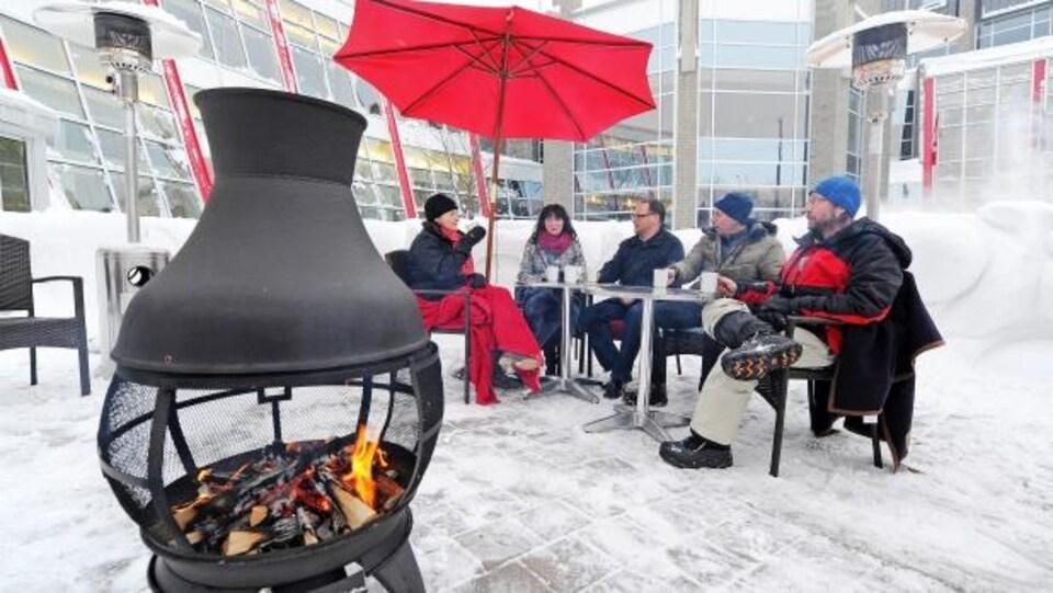 Un groupe de personnes est assis sur une terrasse en plein hiver.