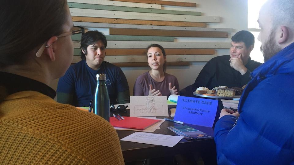 Des gens sont assis autour d'une table et discutent.
