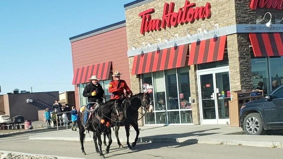 Deux hommes à cheval devant un Tim Hortons.