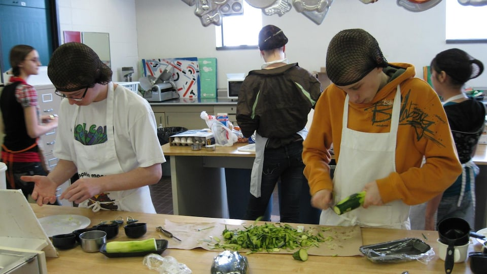 Des jeunes s'affaires à préparer des légumes dans une cuisine d'une école secondaire.