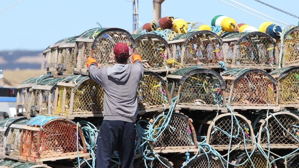 Un pêcheur empile des casiers à homard.
