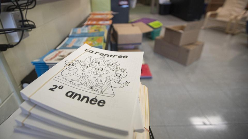 Des cahiers scolaires devant des livres et des boîtes dans une école.