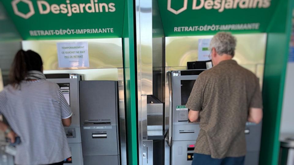 Une femme et un homme à des guichets automatiques de Desjardins.