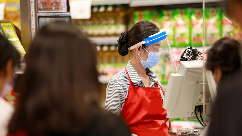 Une caissière de supermarché portant un masque et une visière sert des clients.