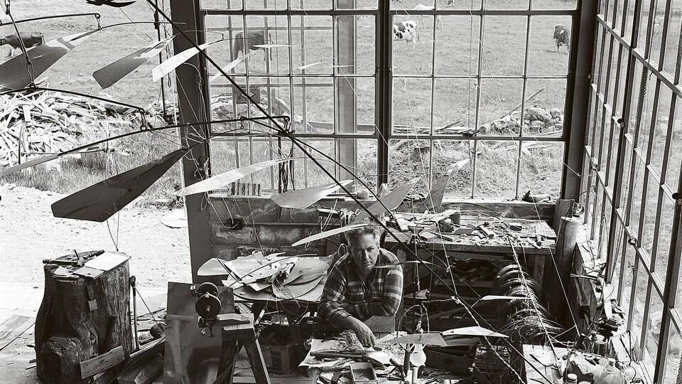Entouré de ses mobiles, Alexander Calder prend la pose dans son atelier de Roxbury dans le Connecticut, en 1941