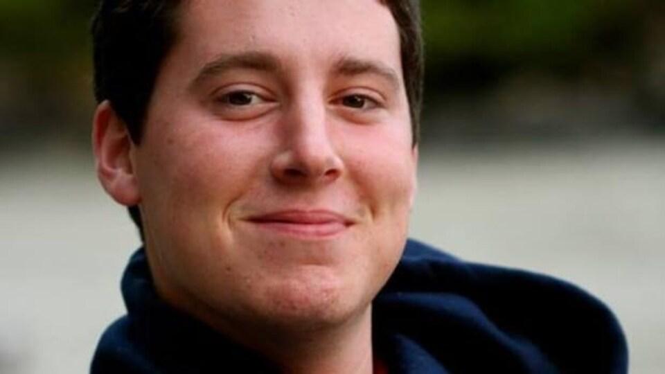 Un jeune homme souriant.