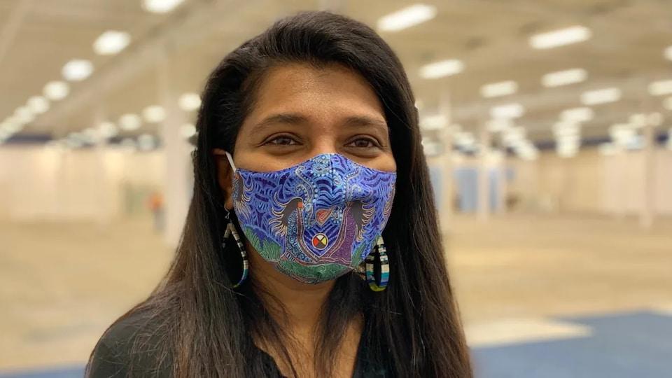 Anila Lee Yuen face caméra avec un masque sur le visage.