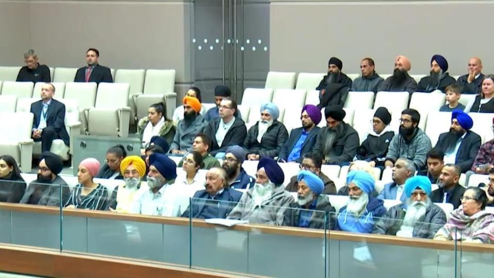Une photo de l'espace réservé au public dans la salle du conseil municipal de Calgary. Plusieurs personnes portant un turban sont assises.