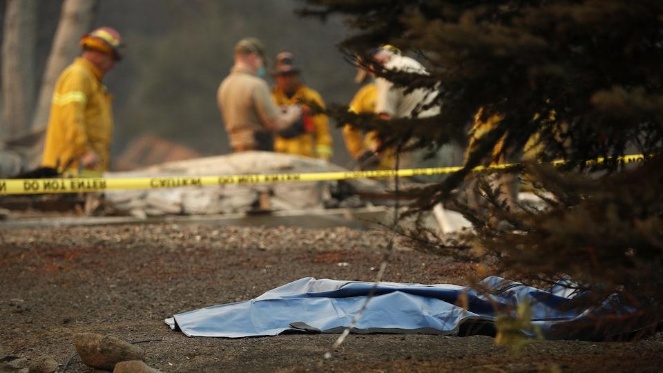 Des pompiers et un corps dans un sac