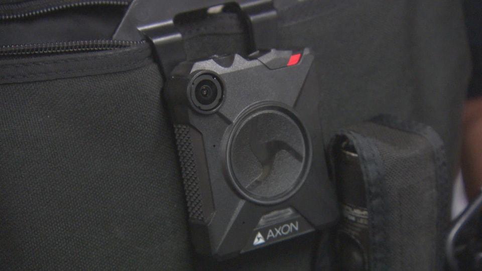 Zoom sur la caméra, plus petite qu'un téléphone cellulaire, sur le gilet d'un policier.