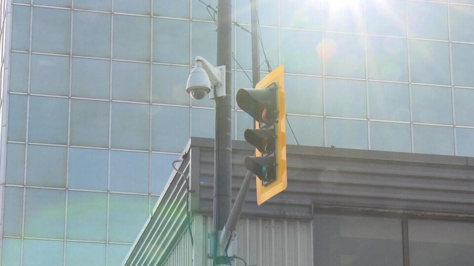 Une petite caméra rotative attachée à un poteau de lumière situé en plein centre-ville.