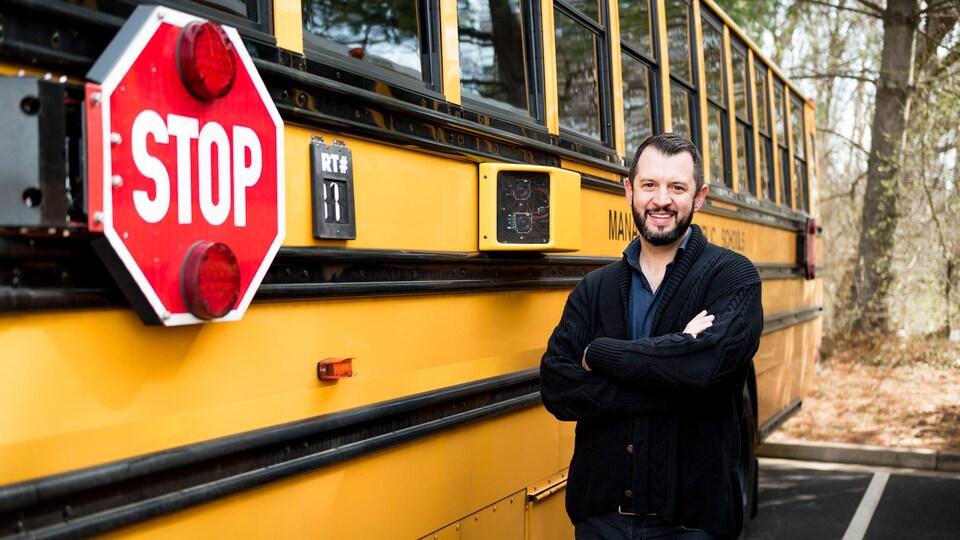 Un homme à côté d'une caméra vidéo installée sur un autobus scolaire.