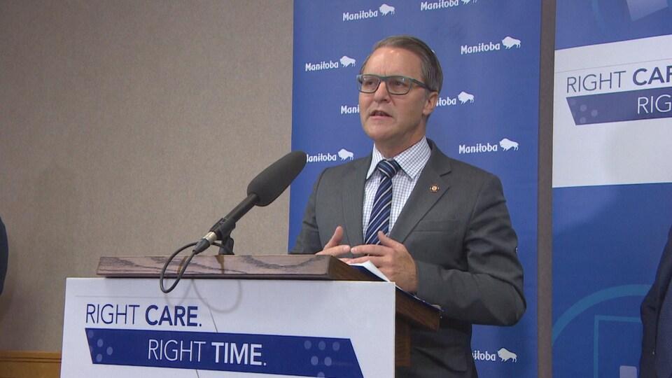 Un homme, avec des lunettes, debout devant un présentoir et un micro. En arrière, un panneau bleu du gouvernement du Manitoba qui dit «Right Care, Right Time».