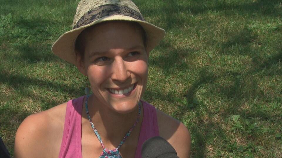 La femme souriante porte un chapeau qui lui fait de l'ombre sur les yeux.