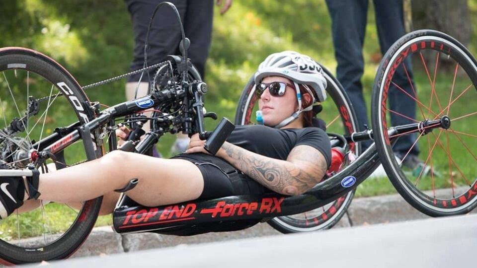 Camille René couchée sur son vélo en habit de compétition
