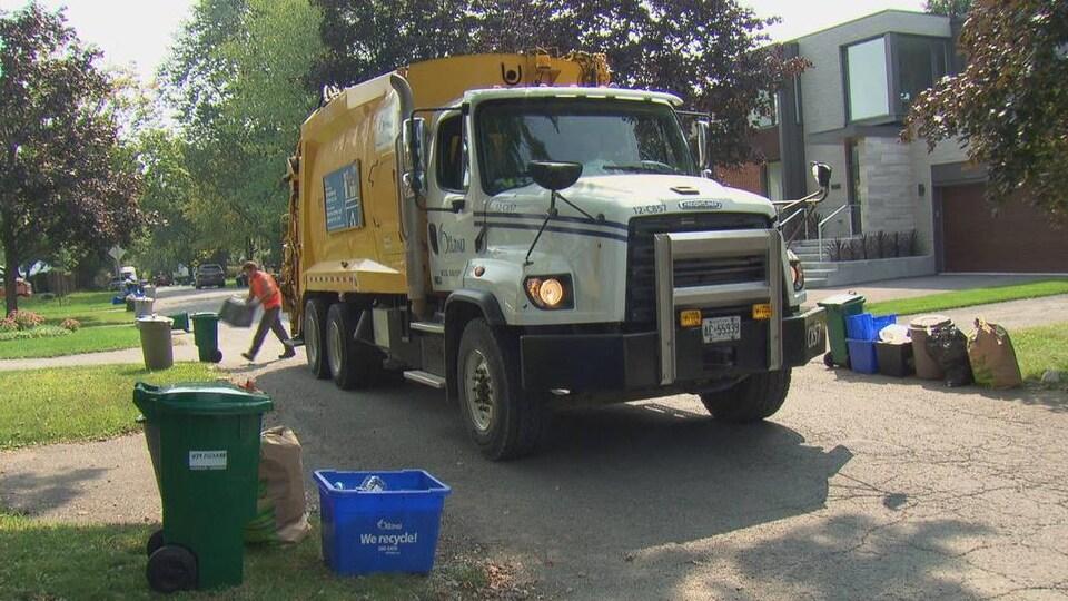 Un camion de collecte d'ordures dans une rue avec des poubelles de recyclage et de compost.