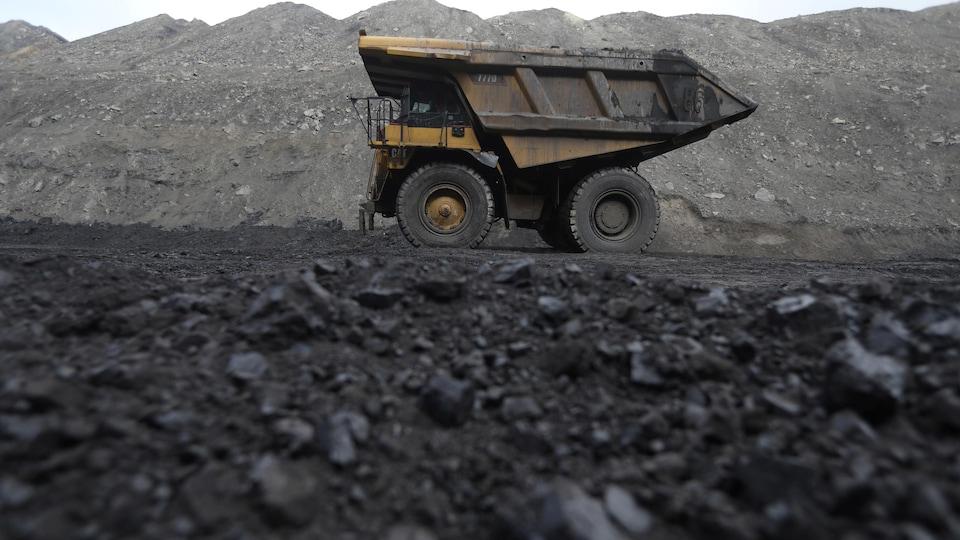 Un camion roule sur une terre noircie par le charbon