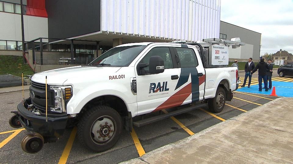 Un camion muni de roues additionnelles pour les voies ferrées est stationné devant le cégep.