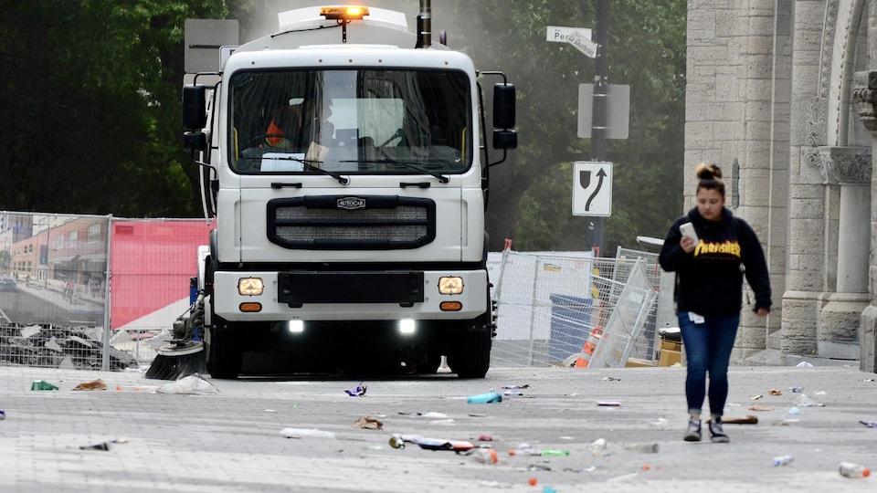 Un camion de nettoyage balaie des détritus sur une rue.