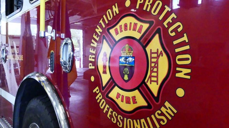 Gros plan sur un camion de pompier où on voit un logo du service d'incendie de Regina avec les mots prévention, protection et professionnalisme.