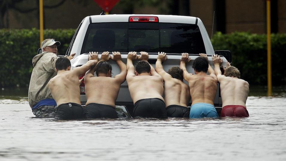 Des hommes poussent un camion bloqué sur une rue inondée de Houston, au Texas.