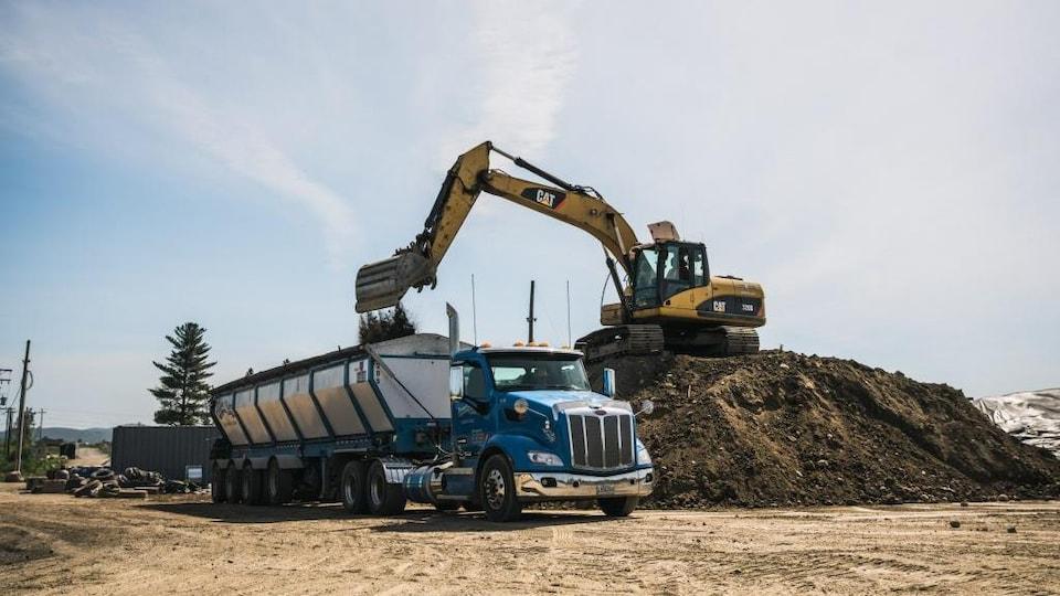 Un camion dans lequel une pelle mécanique déverse de la terre.