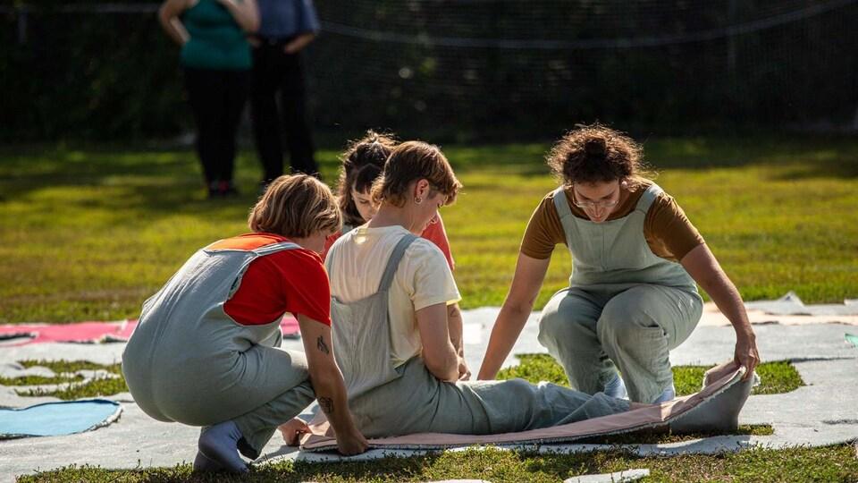 Quatre femmes manipulent une oeuvre textile géante sur le gazon.