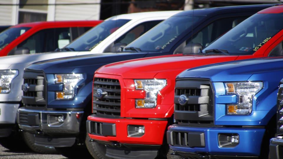 Des camionnettes bleues, rouges et blanche de Ford garées l'une à côté de l'autre