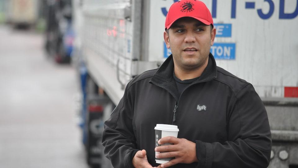 Mehdi Golgoli, café en main, interviewé à côté d'un camion-remorque.