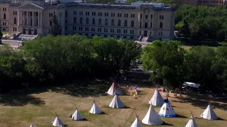 Vue aérienne d'un camp de tipis dans un parc, devant un grand bâtiment de style néo classique.
