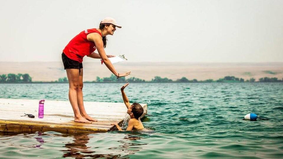 Un enfant se baigne dans un lac, il tape dans la main de sa monitrice qui est sur le quai.