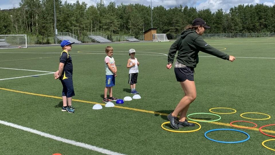 Une jeune fille enjambe des cerceaux posés à terre sur un terrain de soccer pendant que trois enfants la regardent.