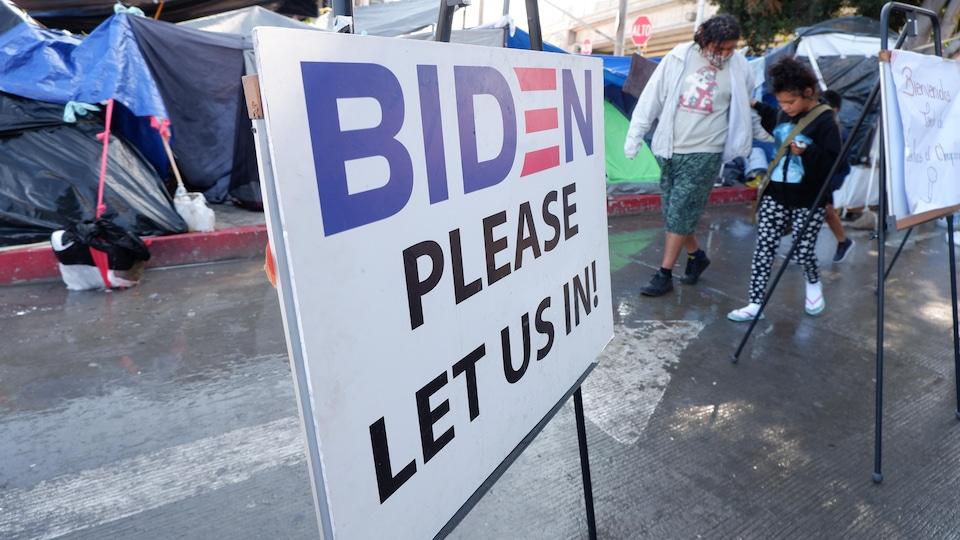 Une affiche demande à Joe Biden de laisser entrer les migrants aux États-Unis.
