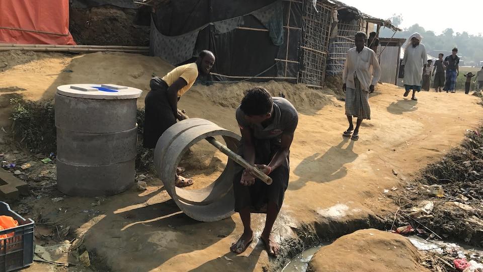 Dans un camp de réfugiés rohingyas, des hommes transportent des cercles de ciment.