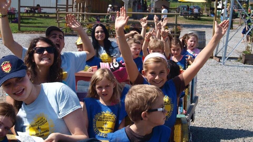 Les enfants et les animateurs sont assis dans un wagon et lèvent les bras au ciel en souriant.