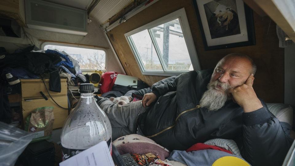 Un homme à la barbe longue couché dans sa roulotte.