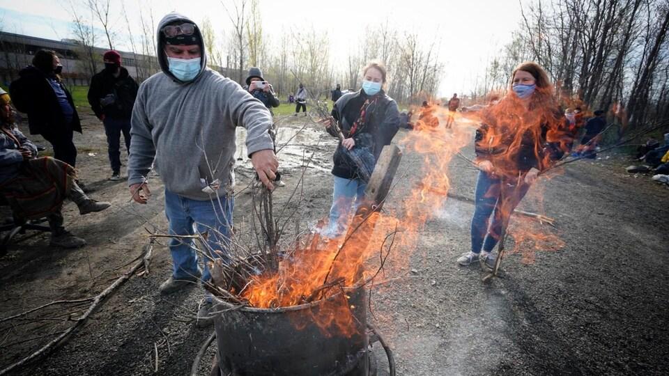 Des personnes dans un boisé autour d'un feu.