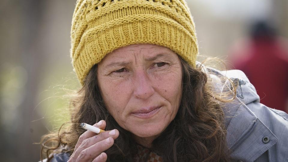 Gros plan d'une femme qui fume une cigarette.
